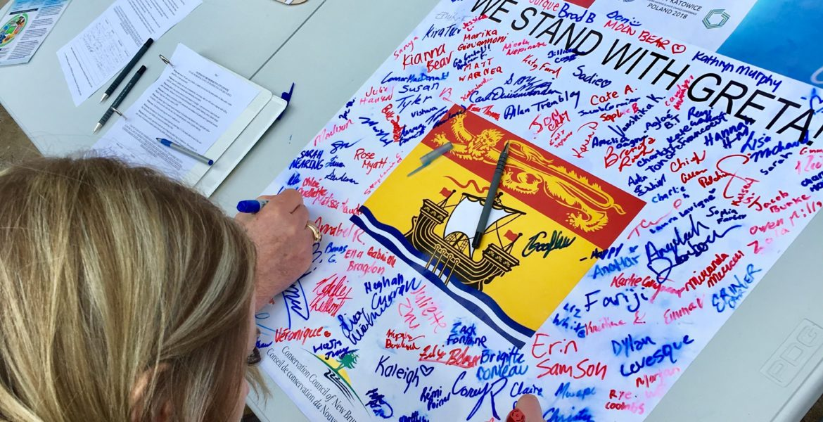 Students sign a poster calling for climate action in New Brunswick during a #FridaysforFuture rally at the New Brunswick Legislature in March 2019.